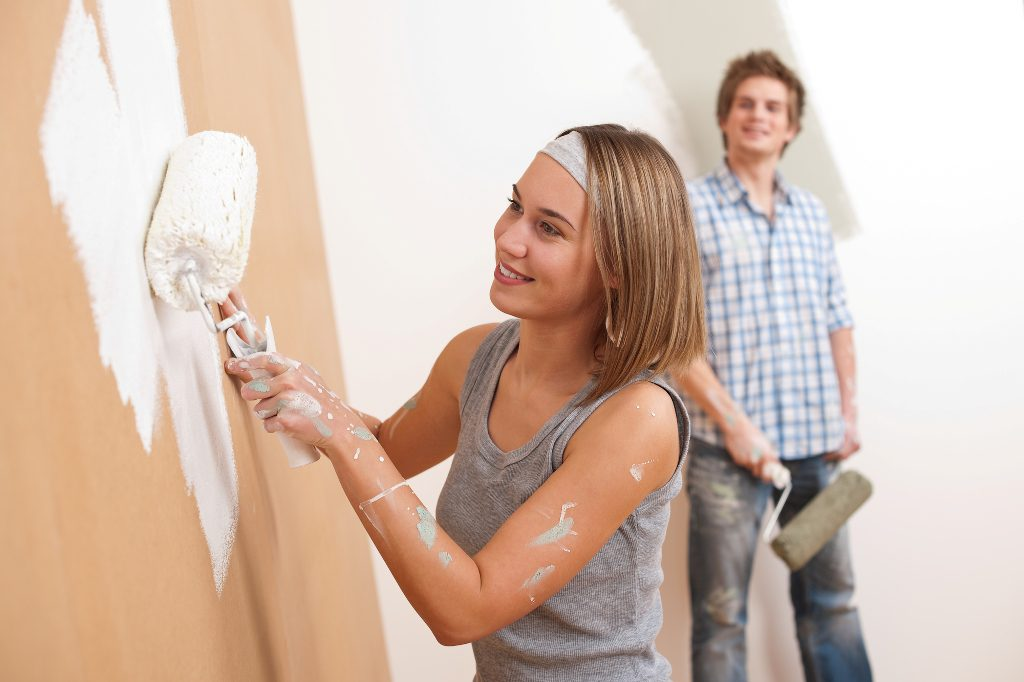 Home improvement: Young man and woman painting wall
