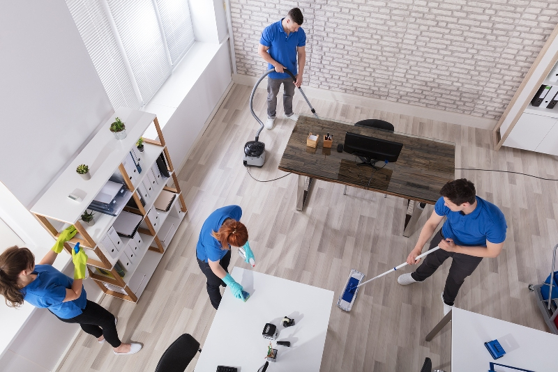 Group Of Janitors In Uniform Cleaning The Office With Cleaning Equipments