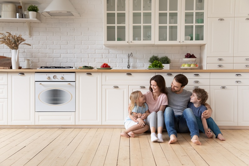 Happy family with children sitting on floor in modern kitchen