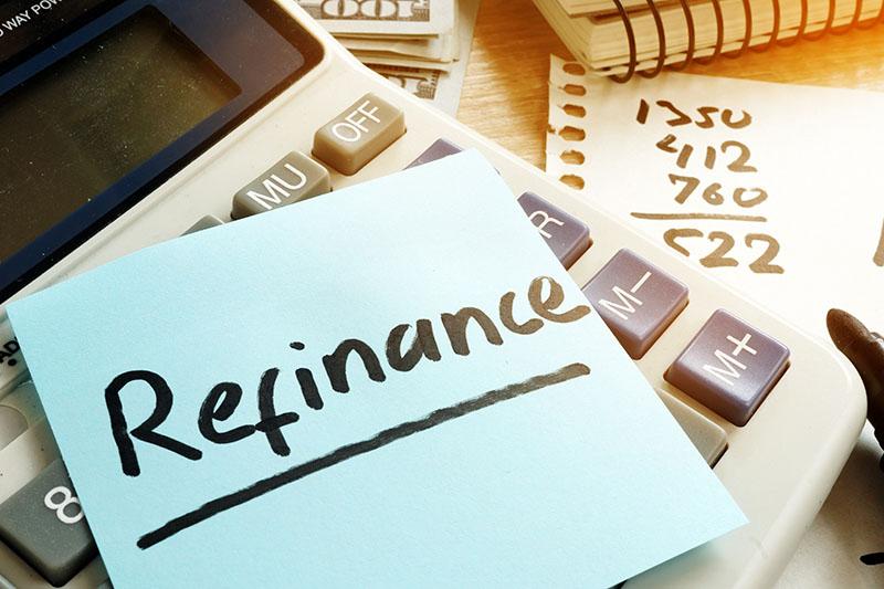 Refinance written on a memo stick and calculator.