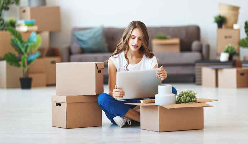 happy young girl with boxes moves to new apartment